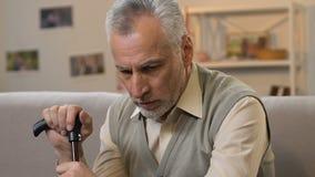 Trauriger älterer Mann mit dem Stock, der zu Hause sitzt und Kamera, Einsamkeit betrachtet stock video
