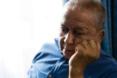Trauriger älterer Mann mit der Hand auf dem Kinn, das durch Fenster sitzt lizenzfreies stockbild