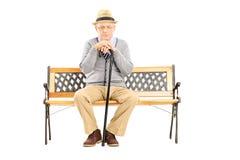 Trauriger älterer Mann mit einem Stock, der auf einer Holzbank sitzt Lizenzfreie Stockfotografie