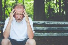 Trauriger alter Mann, der draußen auf Bank brütet stockfotos