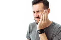 Trauriger bärtiger junger Mann, der Zahnschmerzen auf weißem BAC steht und hat stockfotografie