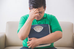 Trauriger beleibter Mann, der eine Gewichtsskala, denkend an sein Gewicht hält Stockfotografie