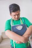 Trauriger beleibter Mann, der eine Gewichtsskala, denkend an sein Gewicht hält Stockbilder