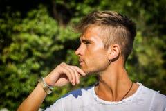 Trauriger, besorgter blonder junger Mann gegen Bäume Lizenzfreies Stockbild