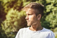 Trauriger, besorgter blonder junger Mann gegen Bäume Stockbilder