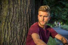 Trauriger, besorgter blonder junger Mann gegen Baum Lizenzfreie Stockfotografie