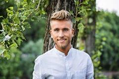 Trauriger, besorgter blonder junger Mann gegen Baum Lizenzfreies Stockfoto