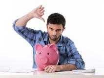 Trauriger besorgter Mann im Druck mit Sparschwein in schlechtem f Stockbild