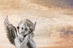 Trauriger betender Engel auf einem orange Himmelshintergrund für ein condolenc Stockfotos