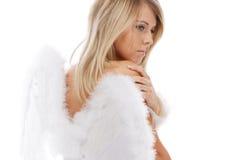 Trauriger blonder Engel, der auf Weiß aufwirft Stockfoto