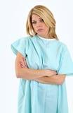 Trauriger blonder Frauenpatient im Krankenhauskleid Lizenzfreies Stockbild