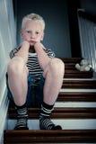 Trauriger blonder Junge sitzt auf Treppe mit Ellbögen auf Knien Lizenzfreies Stockfoto