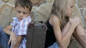 Trauriger Bruder und Schwester sitzen durch die Wand mit einem Koffer zur Tageszeit stock video