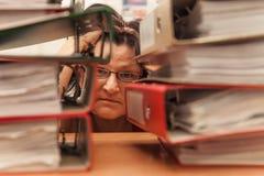 Trauriger Buchhalter mit Stapel Ordnern und fallenden Papieren lizenzfreie stockfotografie