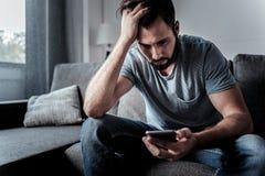 Trauriger düsterer Mann, der eine Mitteilung liest Lizenzfreie Stockbilder