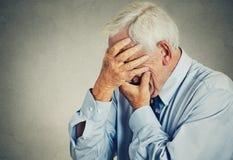 Trauriger deprimierter älterer, alter Mann, der sein Gesicht mit den Händen bedeckt Lizenzfreie Stockfotos