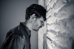Trauriger deprimierter Geschäftsmann, der sich zu Hause im Geisteshilfskonzept einsam fühlt Stockfotografie