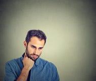 Trauriger deprimierter junger Mann halten Haupt mit der Hand, die unten schaut Stockbild