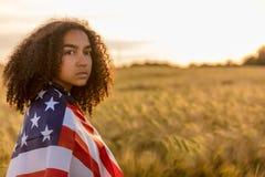 Trauriger deprimierter Mädchen-Frauen-Jugendlicher eingewickelt in USA-Flagge bei Sonnenuntergang Stockfotografie