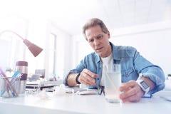 Trauriger deprimierter Mann, der beabsichtigt, seine Medizin zu trinken Lizenzfreies Stockfoto