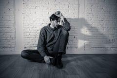 Trauriger deprimierter Mann, der an einer Wand im Konzept der psychischen Gesundheit sich lehnt Lizenzfreie Stockbilder