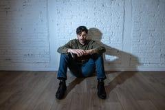 Trauriger deprimierter Mann, der an einer Wand im Konzept der psychischen Gesundheit sich lehnt Stockfoto