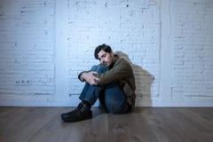 Trauriger deprimierter Mann, der an einer Wand im Konzept der psychischen Gesundheit sich lehnt Stockbilder