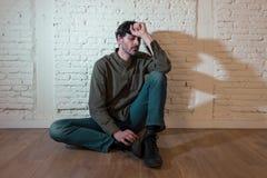 Trauriger deprimierter Mann, der an einer Wand im Konzept der psychischen Gesundheit sich lehnt Lizenzfreies Stockbild