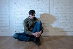 Trauriger deprimierter Mann, der an einer Wand im Konzept der psychischen Gesundheit sich lehnt Lizenzfreies Stockfoto