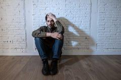Trauriger deprimierter Mann, der an einer Wand im Konzept der psychischen Gesundheit sich lehnt Stockfotografie