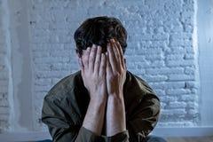 Trauriger deprimierter Mann, der an einer Wand im Konzept der psychischen Gesundheit sich lehnt Lizenzfreie Stockfotografie