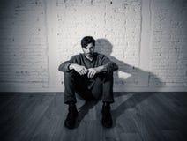 Trauriger deprimierter Mann, der an einer Wand im Konzept der psychischen Gesundheit sich lehnt Stockfotos