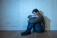 Trauriger deprimierter Mann, der an einer Wand im Konzept der psychischen Gesundheit sich lehnt Lizenzfreie Stockfotos