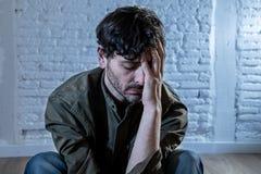 Trauriger deprimierter Mann, der an einer Wand im Konzept der psychischen Gesundheit sich lehnt Stockbild