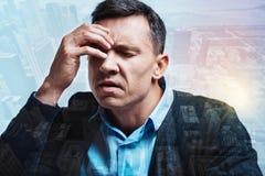 Trauriger deprimierter Mann, der Kopfschmerzen hat Stockbilder