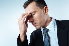 Trauriger deprimierter Mann, der an seine Probleme denkt Stockfotografie