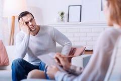 Trauriger deprimierter Mann, der seinen Psychologen betrachtet Lizenzfreies Stockfoto