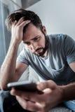 Trauriger deprimierter Mann, der seinen Smartphone hält Stockfoto