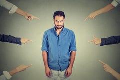 Trauriger deprimierter Umkippenmann, der hinunter viele Finger zeigen auf ihn schaut Stockfoto