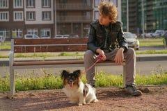 Trauriger einsamer Kerl, der auf einer Bank mit seinem Hund sitzt die Schwierigkeiten von Adoleszenz im Kommunikationskonzept stockbilder