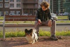 Trauriger einsamer Kerl, der auf einer Bank mit seinem Hund sitzt die Schwierigkeiten von Adoleszenz im Kommunikationskonzept lizenzfreies stockbild