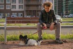 Trauriger einsamer Kerl, der auf einer Bank mit seinem Hund sitzt die Schwierigkeiten von Adoleszenz im Kommunikationskonzept lizenzfreie stockbilder
