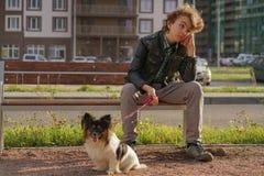 Trauriger einsamer Kerl, der auf einer Bank mit seinem Hund sitzt die Schwierigkeiten von Adoleszenz im Kommunikationskonzept stockfotos