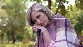 Trauriger einsamer weiblicher sitzender Garten mit Spazierstock, Lebengedächtnisse, Hoffnungslosigkeit lizenzfreies stockfoto