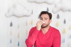Trauriger elender Mann, der die Nase mit einem Papiergewebe abwischt Lizenzfreie Stockfotos