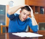 Trauriger entsetzter Kerl, der zu Hause Dokument betrachtet Lizenzfreie Stockbilder
