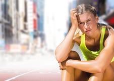 Trauriger enttäuschter Athletenläufer, der sich in der Stadt hinsetzt stockbild