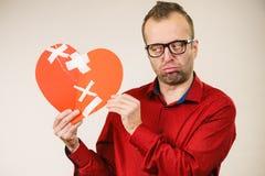 Trauriger erwachsener Mann, der defektes Herz hält stockfotos