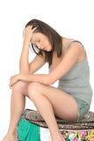 Trauriger Fed Up Tired Young Woman, der auf einem überfließenden vollen Koffer sitzt stockfotografie
