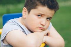 Trauriger fetter Junge, der auf dem Sportsimulator sitzt Lizenzfreie Stockbilder
